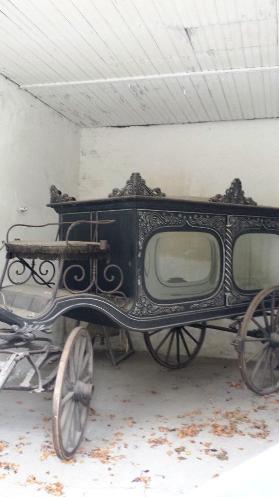 Gegenüber der katholischen Kirche kannst du einen alten Leichenwagen betrachten